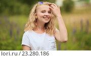 Улыбающаяся девушка подросток на зеленом лугу с сиреневым цветком. Стоковое видео, видеограф Mikhail Davidovich / Фотобанк Лори
