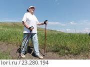 Купить «Пожилая женщина занимается скандинавской ходьбой с палками летом», фото № 23280194, снято 13 июня 2016 г. (c) Наталия Макарова / Фотобанк Лори