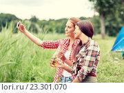 Купить «happy women taking selfie by smartphone at camping», фото № 23301070, снято 25 июля 2015 г. (c) Syda Productions / Фотобанк Лори