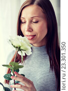Купить «happy woman smelling big white rose at home», фото № 23301350, снято 27 июля 2015 г. (c) Syda Productions / Фотобанк Лори