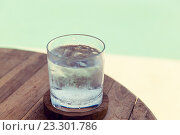 Купить «glass of water with ice cubes on table at beach», фото № 23301786, снято 15 февраля 2015 г. (c) Syda Productions / Фотобанк Лори