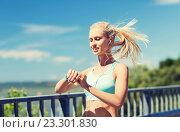 Купить «happy woman with heart rate watch and earphones», фото № 23301830, снято 5 июля 2015 г. (c) Syda Productions / Фотобанк Лори