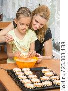 Купить «Мама помогает дочке налить тесто в формочку для кексов», фото № 23303138, снято 3 апреля 2016 г. (c) Иванов Алексей / Фотобанк Лори