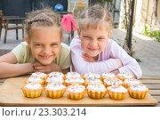 Две девочки корчат смешные рожицы, сидя перед пасхальными кексами. Стоковое фото, фотограф Иванов Алексей / Фотобанк Лори