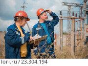 Мужчина и женщина инженеры в синих спецовках и касках осматривают электрическую подстанцию. Стоковое фото, фотограф Станислав Илюк / Фотобанк Лори