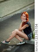 Рыжеволосая девушка сидит на бордюре у тротуара. Стоковое фото, фотограф Никита Вишневецкий / Фотобанк Лори