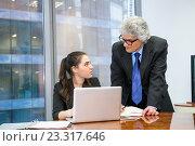Купить «Пожилой бизнесмен помогает молодой сотруднице в офисе», фото № 23317646, снято 13 марта 2016 г. (c) Антон Гвоздиков / Фотобанк Лори