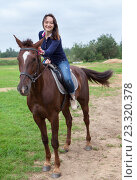 Довольная девушка гладит лошадь по голове во время катания. Стоковое фото, фотограф Кекяляйнен Андрей / Фотобанк Лори