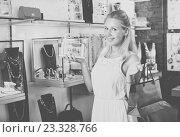 Купить «Portrait of young cheerful woman choosing earrings», фото № 23328766, снято 26 июня 2019 г. (c) Яков Филимонов / Фотобанк Лори