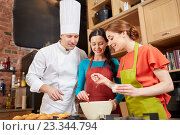 Купить «happy women and chef cook baking in kitchen», фото № 23344794, снято 12 февраля 2015 г. (c) Syda Productions / Фотобанк Лори