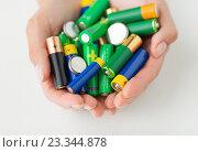 Купить «close up of hands holding alkaline batteries heap», фото № 23344878, снято 3 июня 2016 г. (c) Syda Productions / Фотобанк Лори