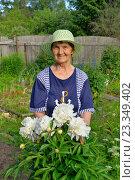 Купить «Пожилая женщина садовод стоит и улыбается рядом с белыми пионами», фото № 23349402, снято 25 июня 2016 г. (c) Максим Мицун / Фотобанк Лори