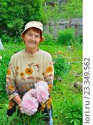 Купить «Пожилая женщина садовод стоит и улыбается рядом с розовыми пионами», фото № 23349562, снято 27 июня 2016 г. (c) Максим Мицун / Фотобанк Лори