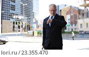 Купить «senior businessman walking with travel bag in city», видеоролик № 23355470, снято 23 июля 2016 г. (c) Syda Productions / Фотобанк Лори
