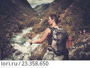 Купить «Woman hiker with backpack standing on the edge of the cliff with epic wild mountain river view.», фото № 23358650, снято 21 июля 2016 г. (c) Andrejs Pidjass / Фотобанк Лори