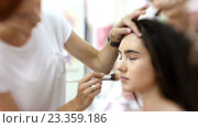 Купить «Визажист делает девушке красивый макияж, парикмахер делает прическу», видеоролик № 23359186, снято 5 августа 2016 г. (c) Константин Шишкин / Фотобанк Лори