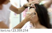 Купить «Визажист делает модели красивый макияж, парикмахер делает прическу», видеоролик № 23359214, снято 5 августа 2016 г. (c) Константин Шишкин / Фотобанк Лори