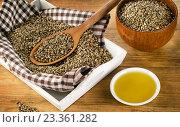 Купить «Hemp seeds and oil on wooden background.», фото № 23361282, снято 16 сентября 2015 г. (c) Tatjana Baibakova / Фотобанк Лори