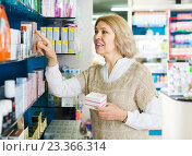 Купить «Female near counter in pharmacy», фото № 23366314, снято 16 августа 2018 г. (c) Яков Филимонов / Фотобанк Лори