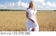 Купить «smiling young woman in white dress on cereal field», видеоролик № 23370386, снято 6 августа 2016 г. (c) Syda Productions / Фотобанк Лори