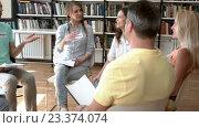 Купить «Smiling people are discussing indoors», видеоролик № 23374074, снято 28 июля 2016 г. (c) Raev Denis / Фотобанк Лори