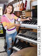 Купить «Positive young girl choosing synthesizer», фото № 23388554, снято 19 августа 2018 г. (c) Яков Филимонов / Фотобанк Лори