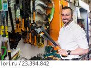 Купить «Man selecting axe in household store», фото № 23394842, снято 17 июля 2018 г. (c) Яков Филимонов / Фотобанк Лори