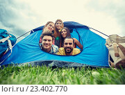 happy friends with backpacks in tent at camping. Стоковое фото, фотограф Syda Productions / Фотобанк Лори