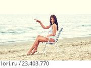 Купить «smiling young woman sunbathing in lounge on beach», фото № 23403770, снято 6 августа 2015 г. (c) Syda Productions / Фотобанк Лори