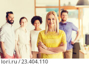 Купить «happy young woman over creative team in office», фото № 23404110, снято 29 марта 2015 г. (c) Syda Productions / Фотобанк Лори
