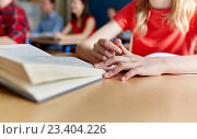 Купить «close up of student with book writing school test», фото № 23404226, снято 22 апреля 2016 г. (c) Syda Productions / Фотобанк Лори