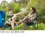 Купить «happy couple clinking drinks at campsite tent», фото № 23404310, снято 27 мая 2016 г. (c) Syda Productions / Фотобанк Лори