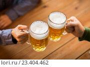Купить «close up of hands with beer mugs at bar or pub», фото № 23404462, снято 22 июля 2016 г. (c) Syda Productions / Фотобанк Лори