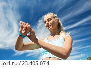 Купить «happy woman with heart rate watch and earphones», фото № 23405074, снято 5 июля 2015 г. (c) Syda Productions / Фотобанк Лори