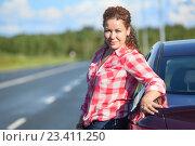 Купить «Девушка автомобилистка в красной клетчатой рубашке стоит рядом с автомобилем», фото № 23411250, снято 12 августа 2016 г. (c) Кекяляйнен Андрей / Фотобанк Лори