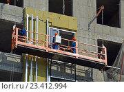 Купить «Рабочие-высотники в люльке монтируют утеплитель на строительстве современного нового здания», эксклюзивное фото № 23412994, снято 15 мая 2014 г. (c) Александр Замараев / Фотобанк Лори