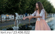 Купить «Девушка играет с фонтаном в городском парке», видеоролик № 23436022, снято 26 августа 2016 г. (c) Игорь Усачев / Фотобанк Лори