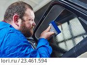 Купить «car tinting. Automobile mechanic technician applying foil», фото № 23461594, снято 14 апреля 2016 г. (c) Дмитрий Калиновский / Фотобанк Лори