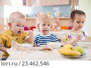 Купить «Маленькие дети обедают в детском саду», фото № 23462546, снято 1 мая 2016 г. (c) Андрей Кузьмин / Фотобанк Лори