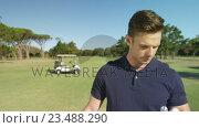 Купить «Happy golf player examining the golf ball», видеоролик № 23488290, снято 22 июля 2019 г. (c) Wavebreak Media / Фотобанк Лори