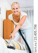 Купить «Housewife vacuuming floor and furniture», фото № 23495798, снято 17 августа 2018 г. (c) Яков Филимонов / Фотобанк Лори