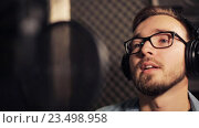 Купить «man with headphones singing at recording studio», видеоролик № 23498958, снято 25 августа 2016 г. (c) Syda Productions / Фотобанк Лори