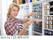 Купить «Mature glad woman customer picking various buttons», фото № 23499614, снято 14 июля 2020 г. (c) Яков Филимонов / Фотобанк Лори