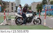 Купить «Инструктор и начинающий мотоциклист на автодроме, выезд из гаража», видеоролик № 23503870, снято 21 августа 2016 г. (c) Кекяляйнен Андрей / Фотобанк Лори