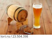 Купить «close up of beer glass, peanuts and wooden barrel», фото № 23504398, снято 22 июля 2016 г. (c) Syda Productions / Фотобанк Лори