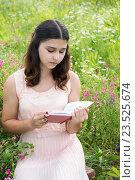 Купить «dark-haired girl reading a book on nature», фото № 23525674, снято 8 июля 2016 г. (c) Володина Ольга / Фотобанк Лори