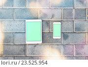 Смартфон и планшетный ПК на фоне кирпичной стены. Стоковое фото, фотограф ouh_desire / Фотобанк Лори