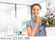 Купить «Portrait of smiling afro-american office worker decorating christmas tree in offfice», фото № 23531398, снято 13 декабря 2014 г. (c) Sergey Nivens / Фотобанк Лори
