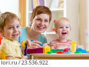 Купить «woman playing and teaching children», фото № 23536922, снято 26 декабря 2014 г. (c) Оксана Кузьмина / Фотобанк Лори