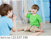 Купить «kids brothers talking with tin can telephone», фото № 23537190, снято 7 февраля 2015 г. (c) Оксана Кузьмина / Фотобанк Лори